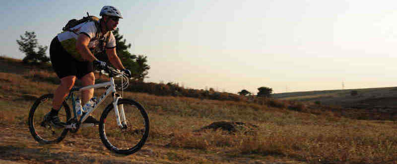 A heavy-set man rides a mountain bike down a hill.